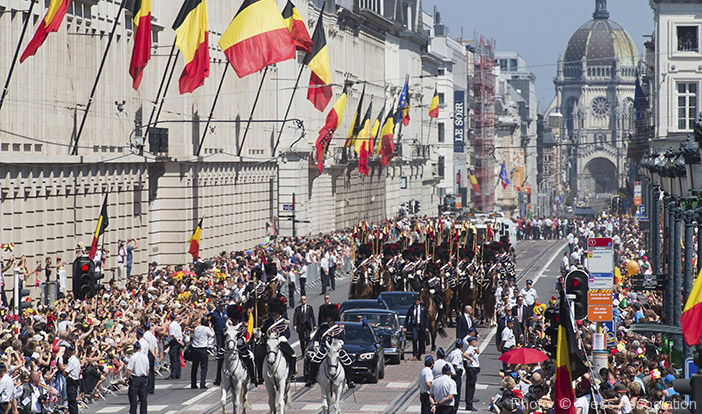 King Philippe and Queen Mathilde, second car from left, ride in a parade during the celebrations in Brussels.