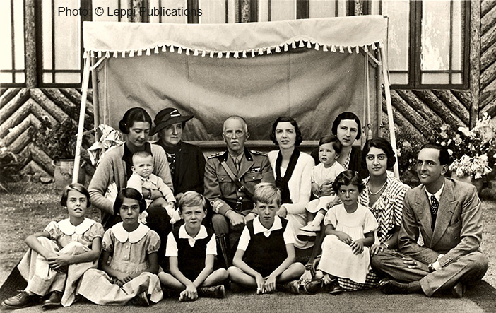 The return of the Savoys: August 1934: King Victor Emmanuel and Queen Elena of Italy with their children and grandchildren. From left to right:: Jolanda with son Pier Francesco, Queen Elena, King Vittorio Emanuele III, Mafalda, Giovanna holding her daughter Maria-Luisa, youngest daughter Maria and Umberto. Front row, from left to right, Princess Jolanda's children: Vittoria Francesca, Maria Ludovia and, on her Aunt Maria's lap Guia Anna Maria. The two boys are Princess Mafalda's children, Enrico and her eldest son Maurizio. Princess Maria José was not present for this photograph as she was pregnant with her first child, Maria Pia.