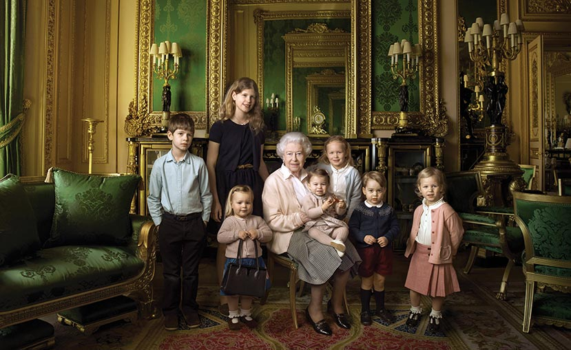 An official portrait by Annie Liebowitz for the Queen's 90th birthday. The Queen with her great-grandchildren and youngest grandchildren. From left: James, Viscount Severn; Lady Louise Windsor; Mia Tindall (holding the Queen's handbag); Princess Charlotte; Savannah Phillips; Prince George and Isla Phillips.